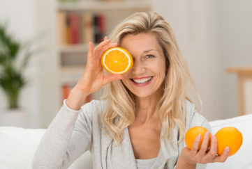 Woman holding up half an orange to the side of her face