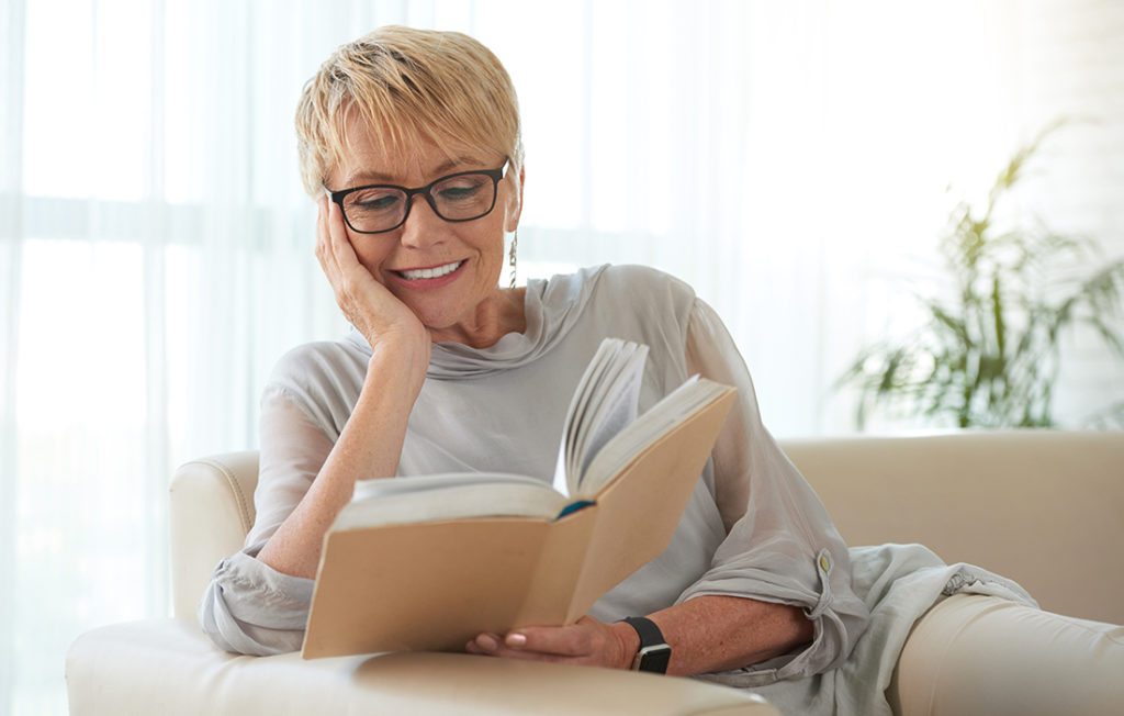 Senior blond woman in glasses resting on sofa and reading a book