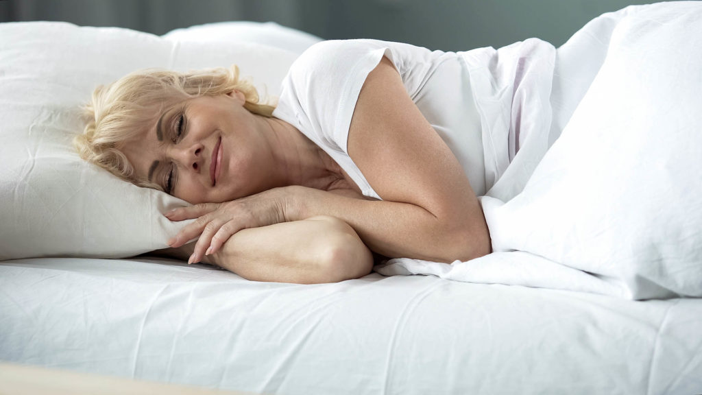 Happy middle-aged female sleeping in bed on orthopedic mattress, healthy rest;
