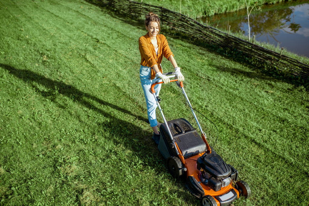 Beautiful young woman cutting grass with gasoline lawn mower, gardening on the backyard in the countryside, view from above;