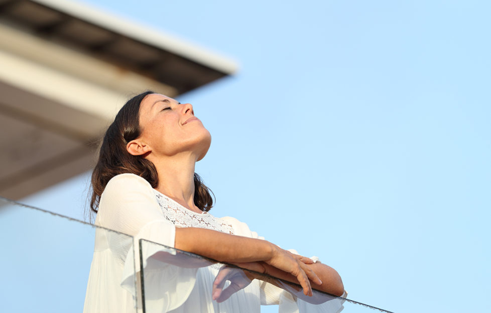 Relaxed adult woman breathing fresh air standing on a hotel balcony