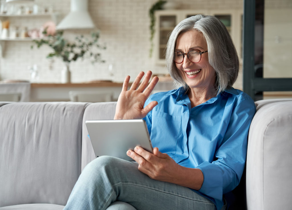 Happy 60s older mature middle aged adult woman waving hand holding digital tablet computer video conference calling by social distance virtual family online chat meeting sitting on couch at home.;