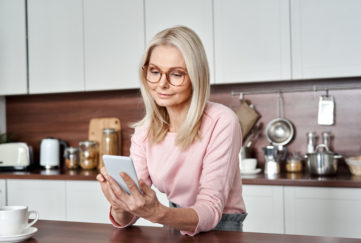 Middle aged 50 years old woman using apps ordering buying food on smartphone sitting in kitchen at home. Mature older lady holding mobile phone texting messages, browsing online services.;