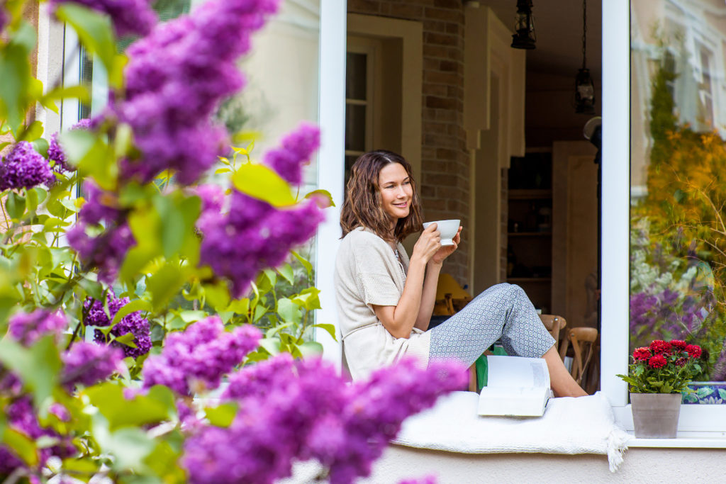 Smiling beautiful middle-aged woman with a cup of hot drink on the windowsill in the garden with blooming lilac;