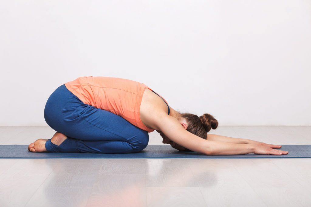 Woman relax in Hatha yoga asana Balasana - child's pose resting position or counter asana for many asanas on yoga mat on yoga mat in studio on grey background