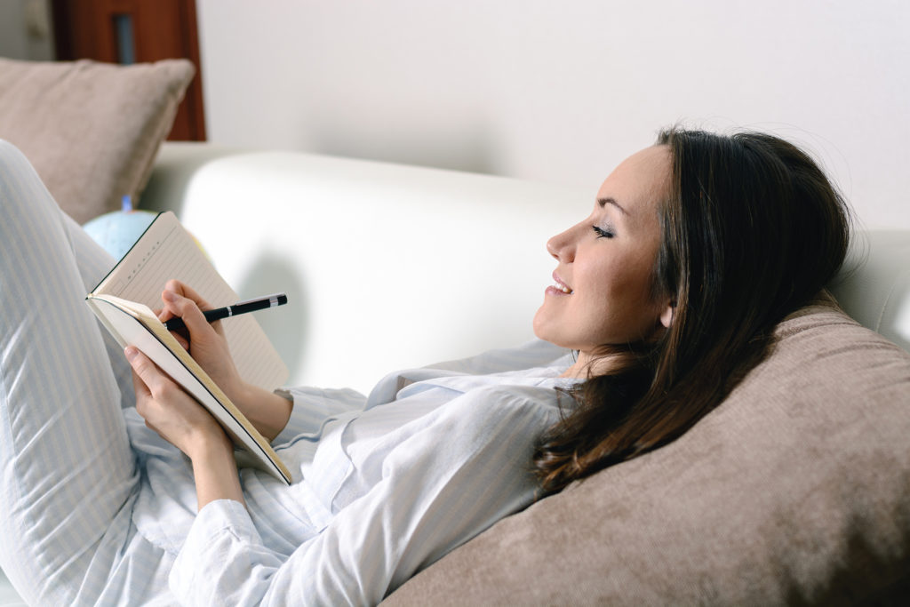 Satisfied and happy smiling girl lying on the sofa in the room and writes a journal of your dreams, plans, goals, experiences, ideas, lived emotions and feelings.;