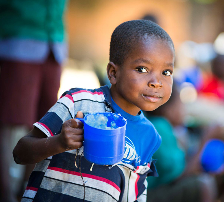 A young boy eating porridge
