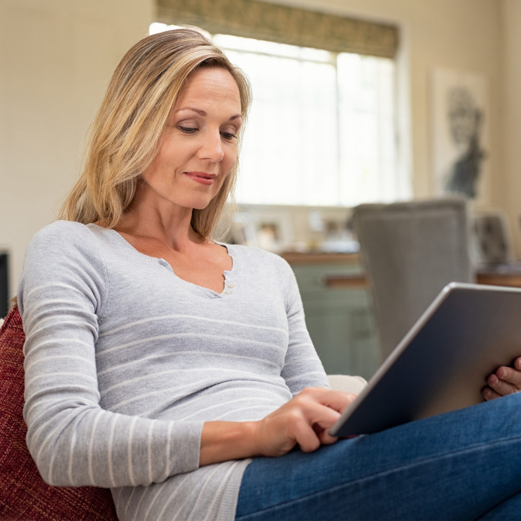 mature woman sitting on couch and using digital tablet. Smiling lady browsing internet over tablet at home