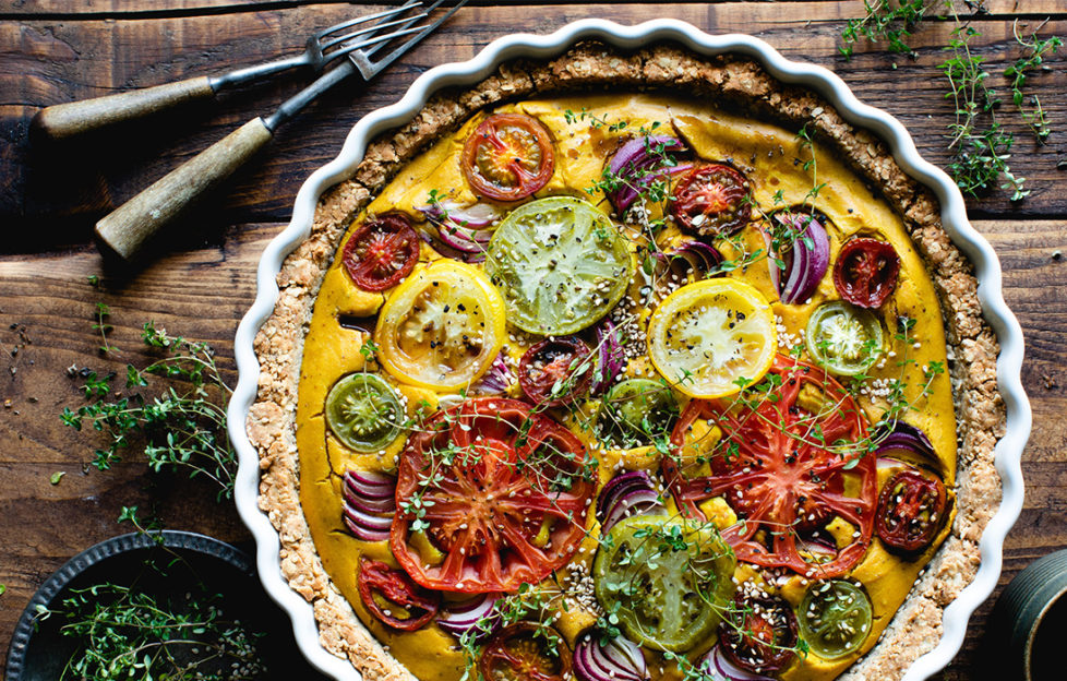 vegan quiche made with tofu and hazelnuts, topped with different coloured tomatoes and thyme sprigs