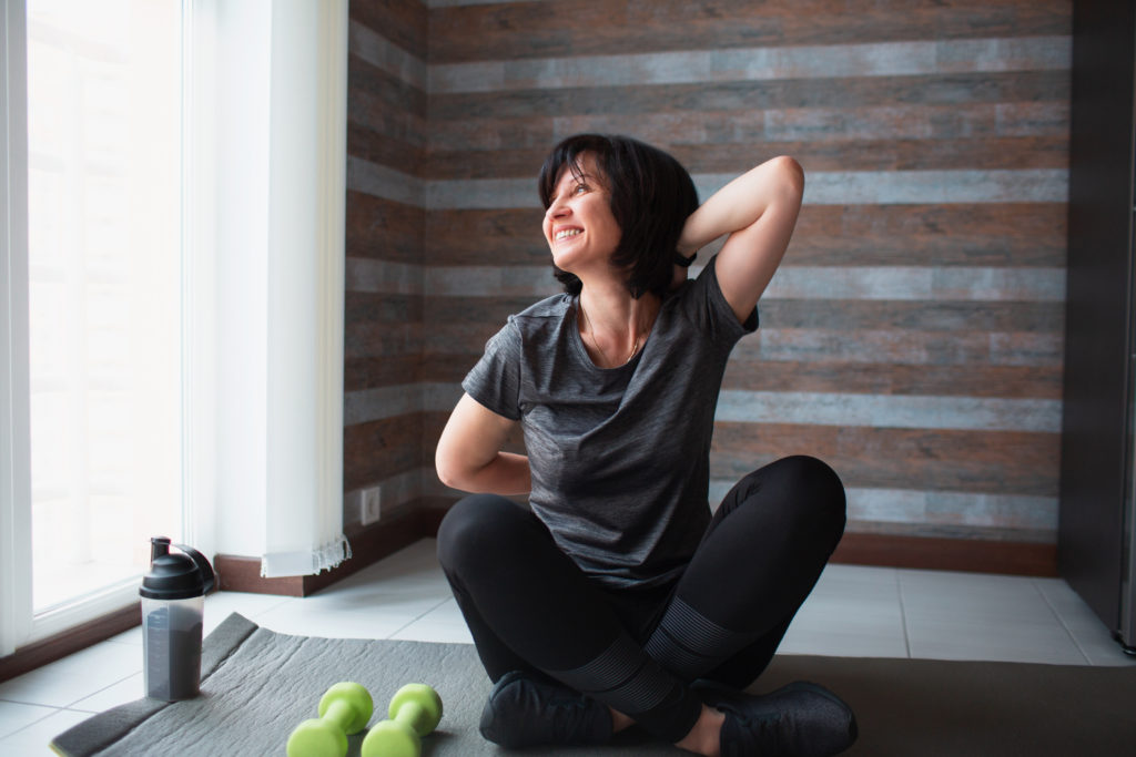 Adult fit slim woman has workout at home. Amazing positive female mature person hold hands together on back and look with smile on window. Stretching arms and exercising.;