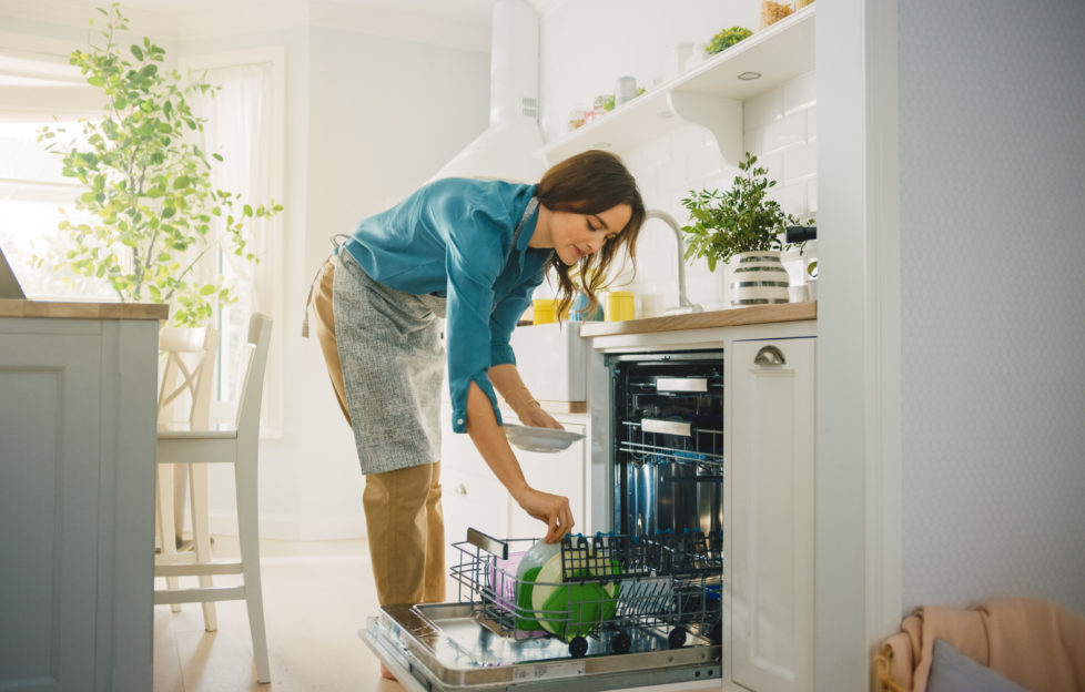 Beautiful Female is Loading Dirty Plates into a Dishwasher Machine in a Bright Sunny Kitchen. Girl in Wearing an Apron. Young Housewife Uses Modern Appliance to Keep the Home Clean.;
