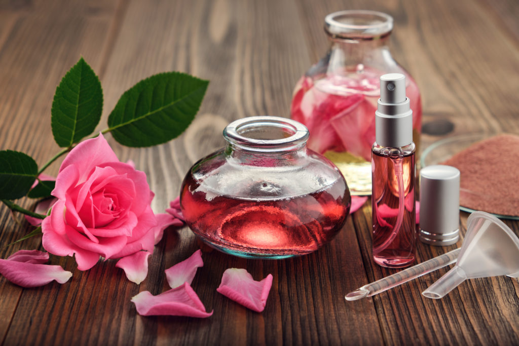 Rose flower, infused water and essential oil or rose blend bottle, flavored water in a spray bottle, pink clay powder, glass spatula and small funnel for making of cosmetic products at home.
