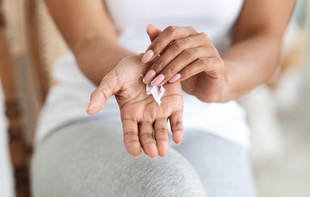 Woman rubbing moisturiser on her hand