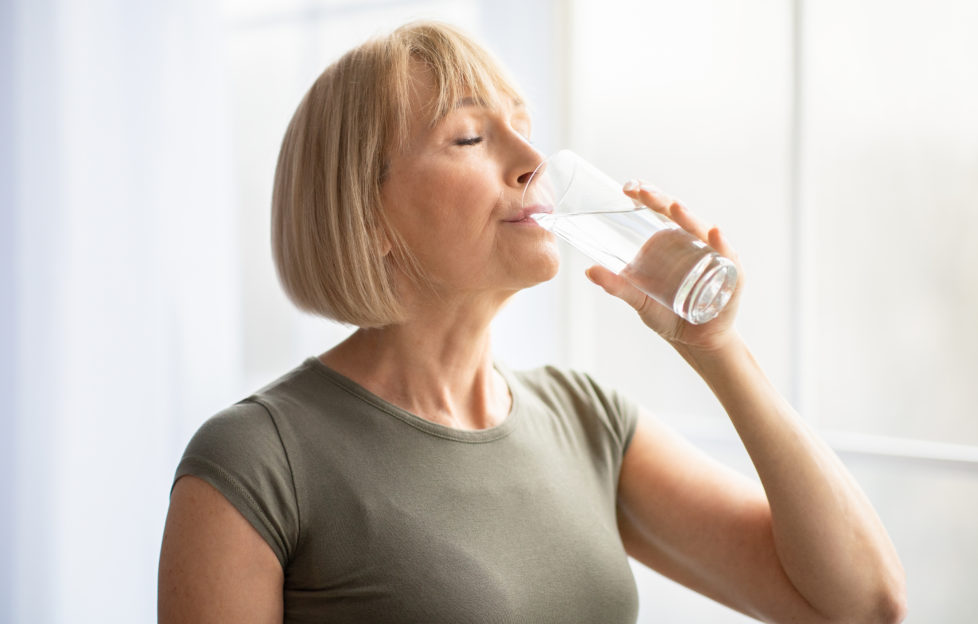 Fit senior woman drinking clear water during her workout break at home. Mature Caucasian lady staying hydrated after sports training. Healthy lifestyle and wellness concept;