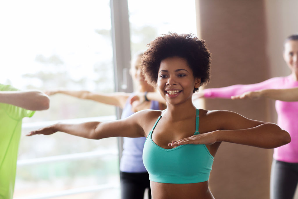 fitness, sport, dance and lifestyle concept - group of smiling people with coach dancing zumba in gym or studio;