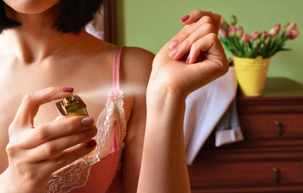 Woman puts perfume on. Perfume bottle in hand. Perfume spraying. Perfume;