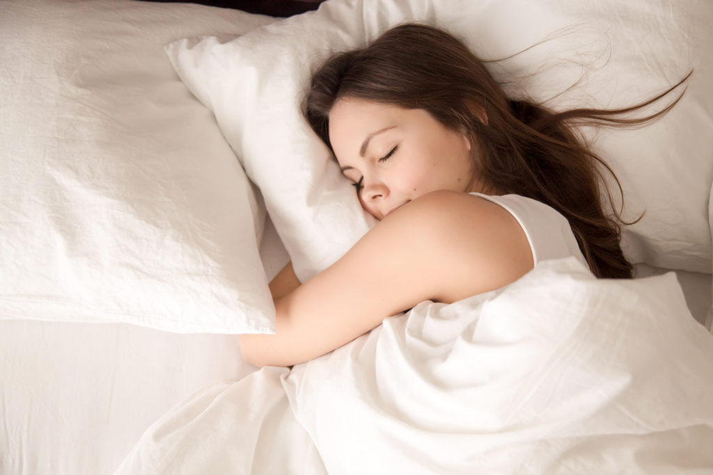 Top view of attractive young woman sleeping well in bed hugging soft white pillow. Teenage girl resting, good night sleep concept. Lady enjoys fresh soft bedding linen and mattress in bedroom ;