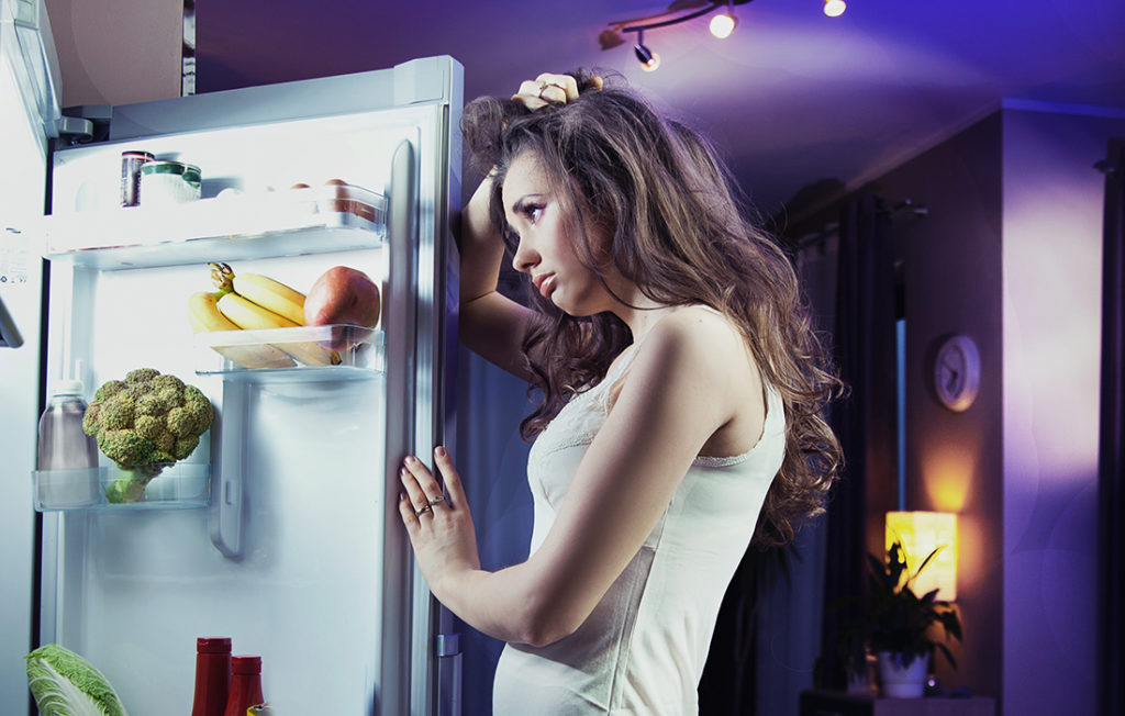 Young woman looking at fridge;