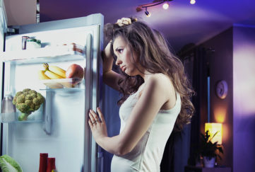 Young woman looking at fridge;