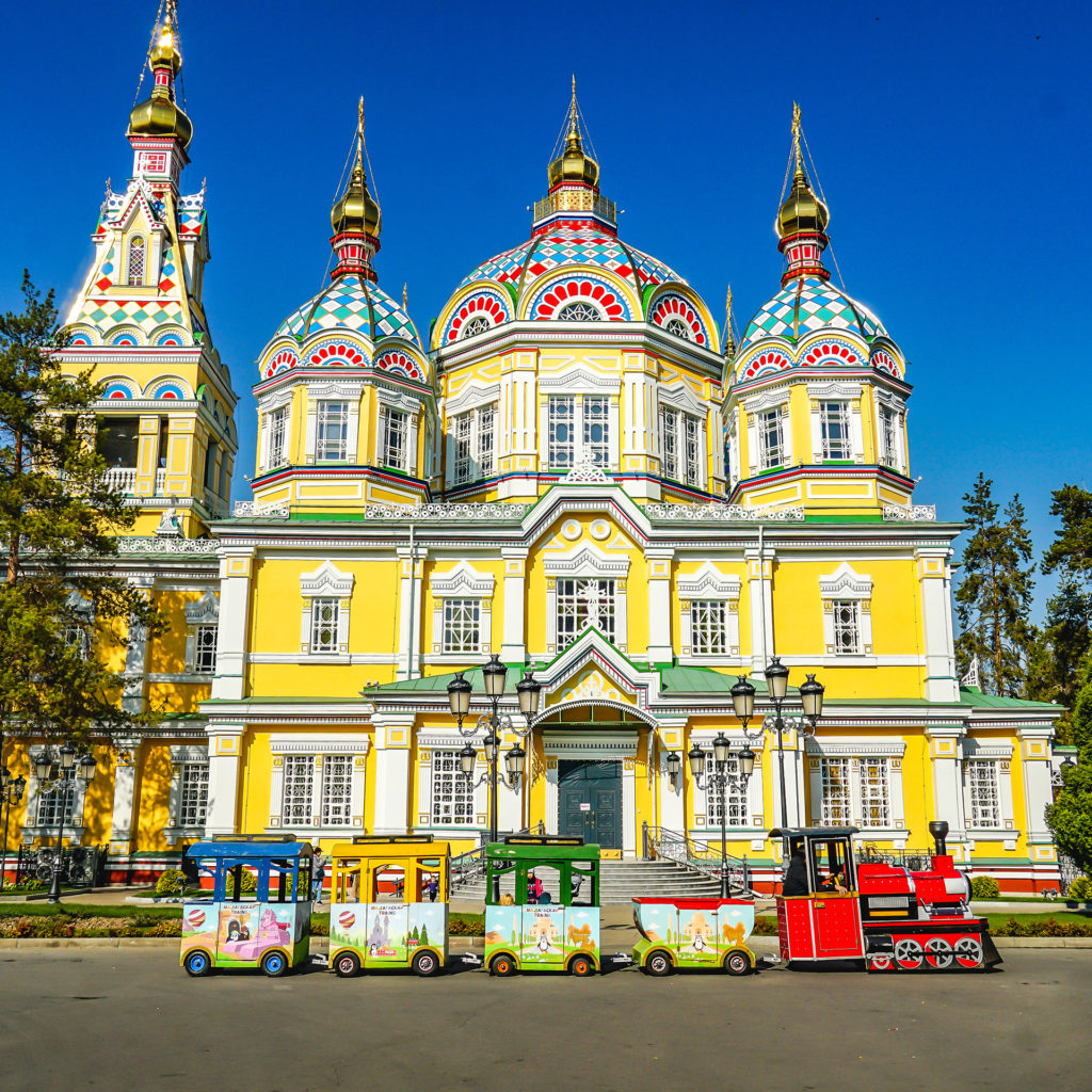Colorful painted historical Ascension Cathedral Russian Orthodox Church in Almaty, Kazakhstan in the park with trackless amusement train for kid