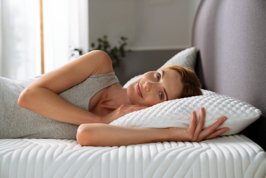 Woman lying in bed resting on pillow