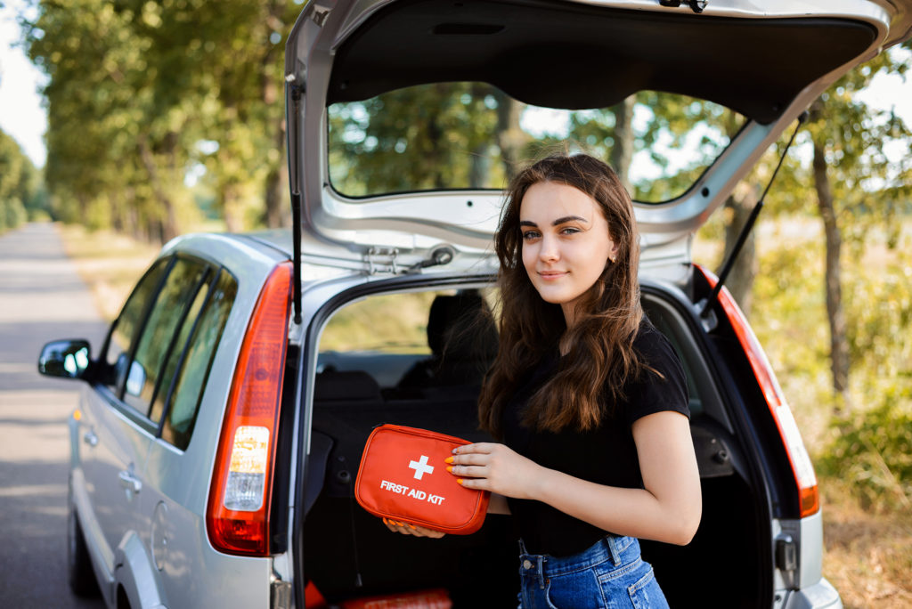 Young girl standing near open back door of silver hatchback car and shows first aid kit that must be in every car for emergency; Shutterstock ID 1464201608