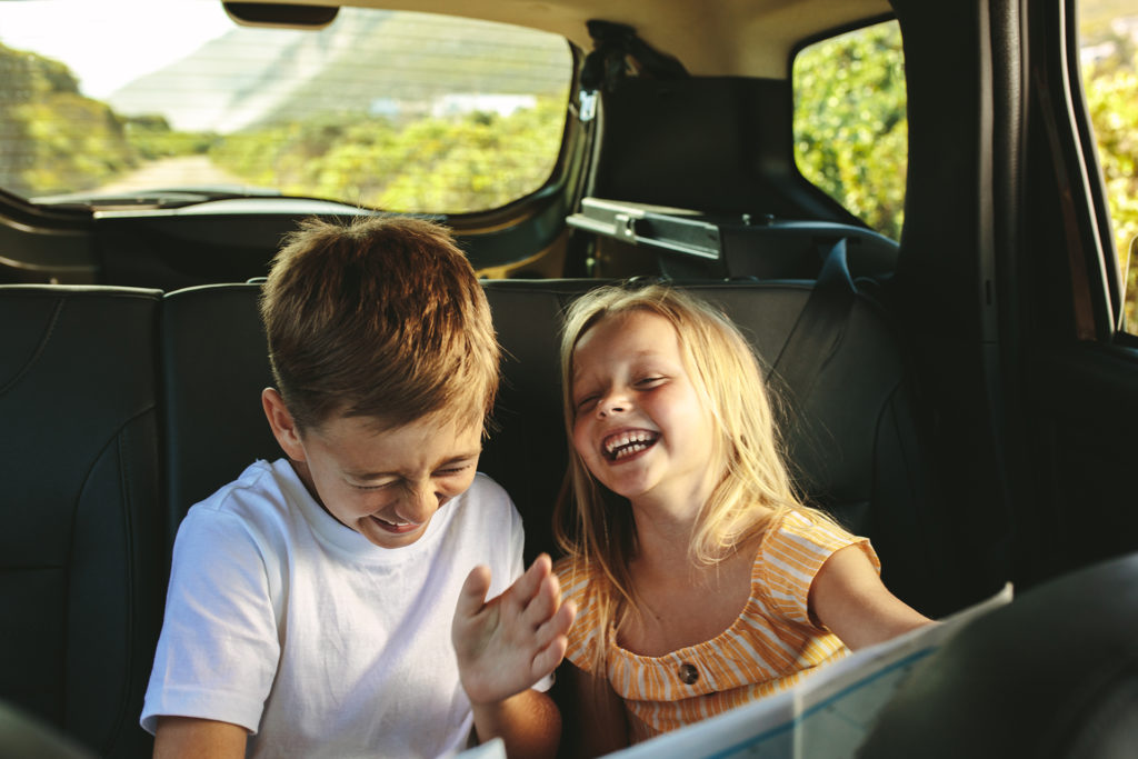 Siblings sitting on backseat of car looking at map and smiling. Kids traveling in a car on roadtrip playing with a map.; Shutterstock ID 1790116736