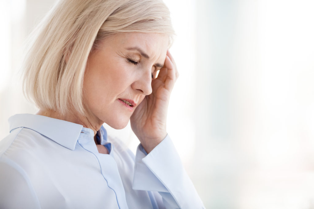 Tired upset mature old businesswoman suffering from strong chronic headache migraine or memory loss at work, stressed dizzy fatigued middle aged senior woman office worker feels pain in aching head;