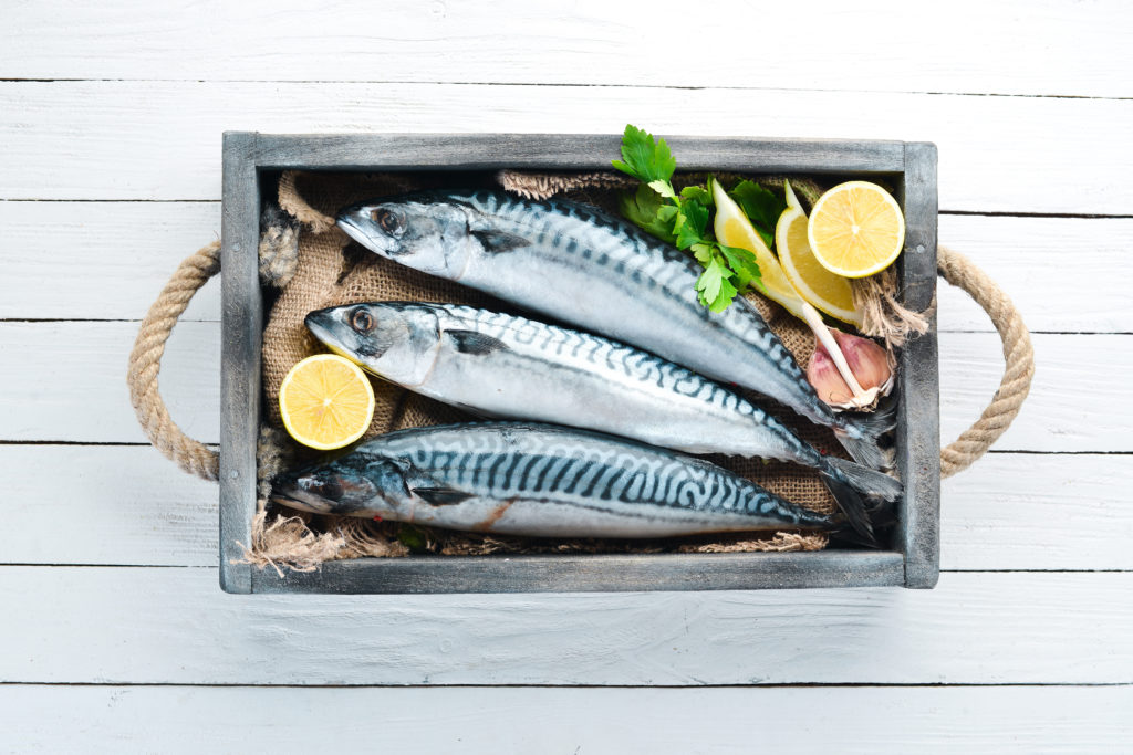 Mackerel on a white wooden background. Raw fish Top view.