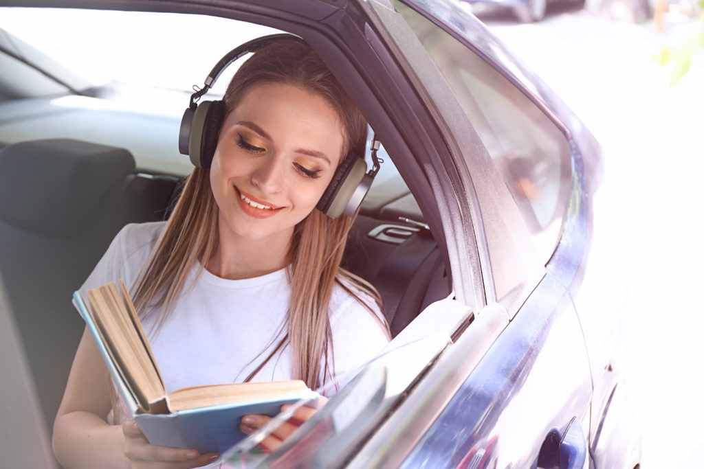 Beautiful young woman listening to music while reading book in car;