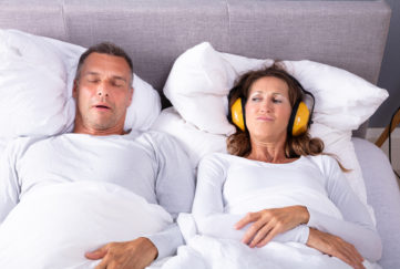 Mature Woman Covering Her Ears With Headphone While Man Snoring In Bed;