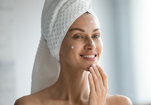 Lady applying skin cream on face Pic: Shutterstock
