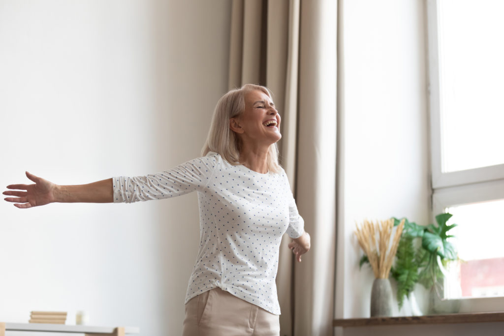 Laughing carefree middle-aged woman standing in living room stretched hands closed eyes breathing fresh air feels happy healthy, starts new day positive mood and thoughts, dancing enjoy life concept;