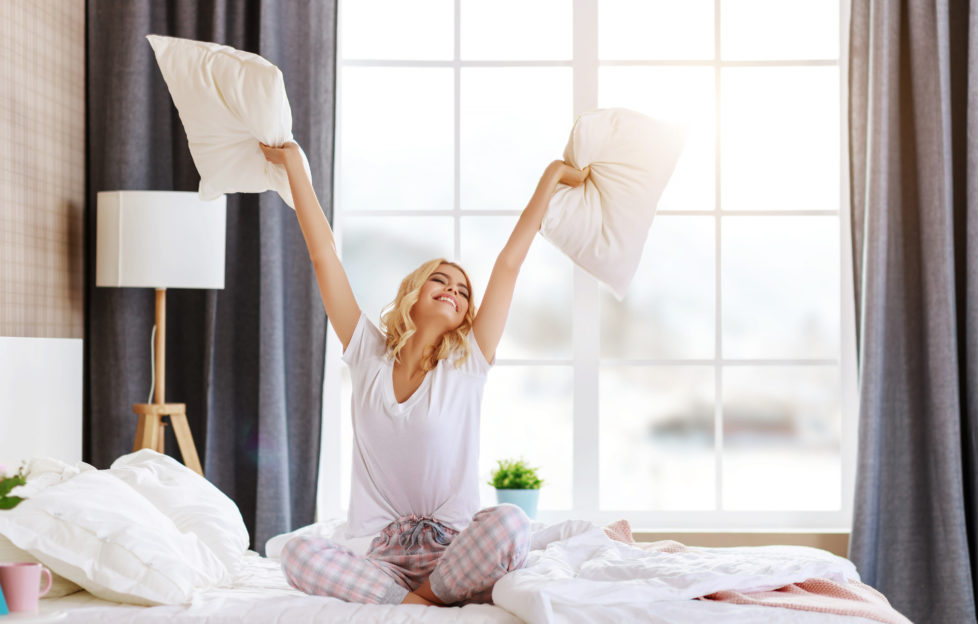 happy young woman laughing and jumping on the bed in the morning at home ;