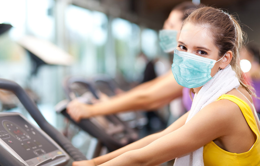 Group of people doing fitness in a gym wearing a mask, coronavirus concept;