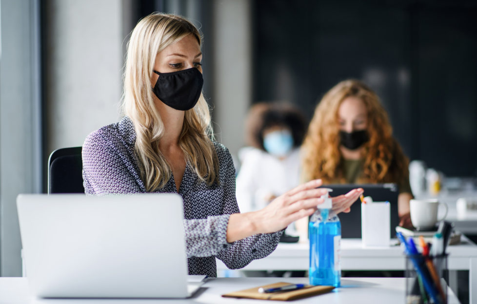 Young woman with face mask back at work in office after lockdown, disinfecting hands.