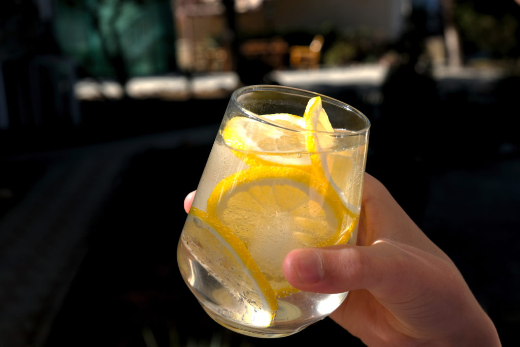 A fresh cocktail made with ginger beer, lime and ice. Drink in hand. ;