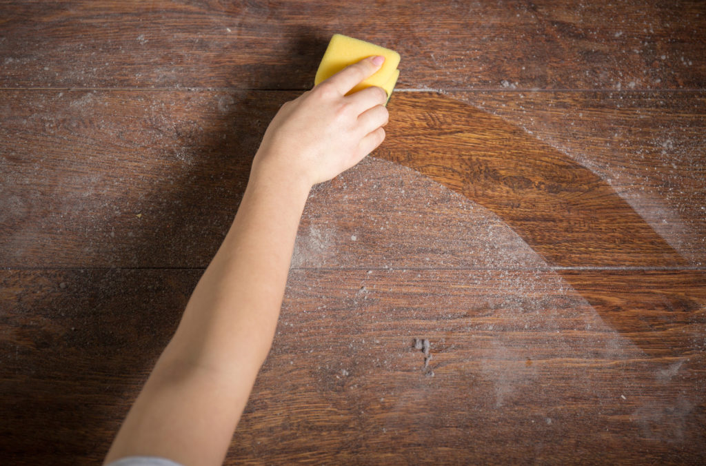 Using yellow sponge for cleaning dusty wood;