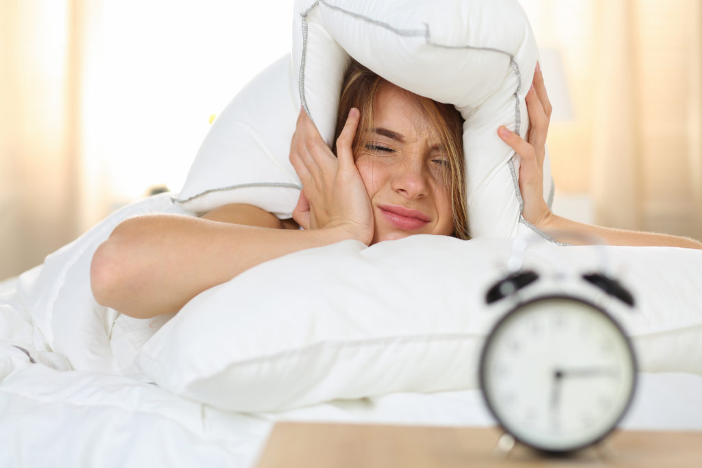 Young beautiful blonde woman lying in bed suffering from alarm clock sound covering head and ears with pillow making unpleasant face. Early wake up, not getting enough sleep, going work concept;