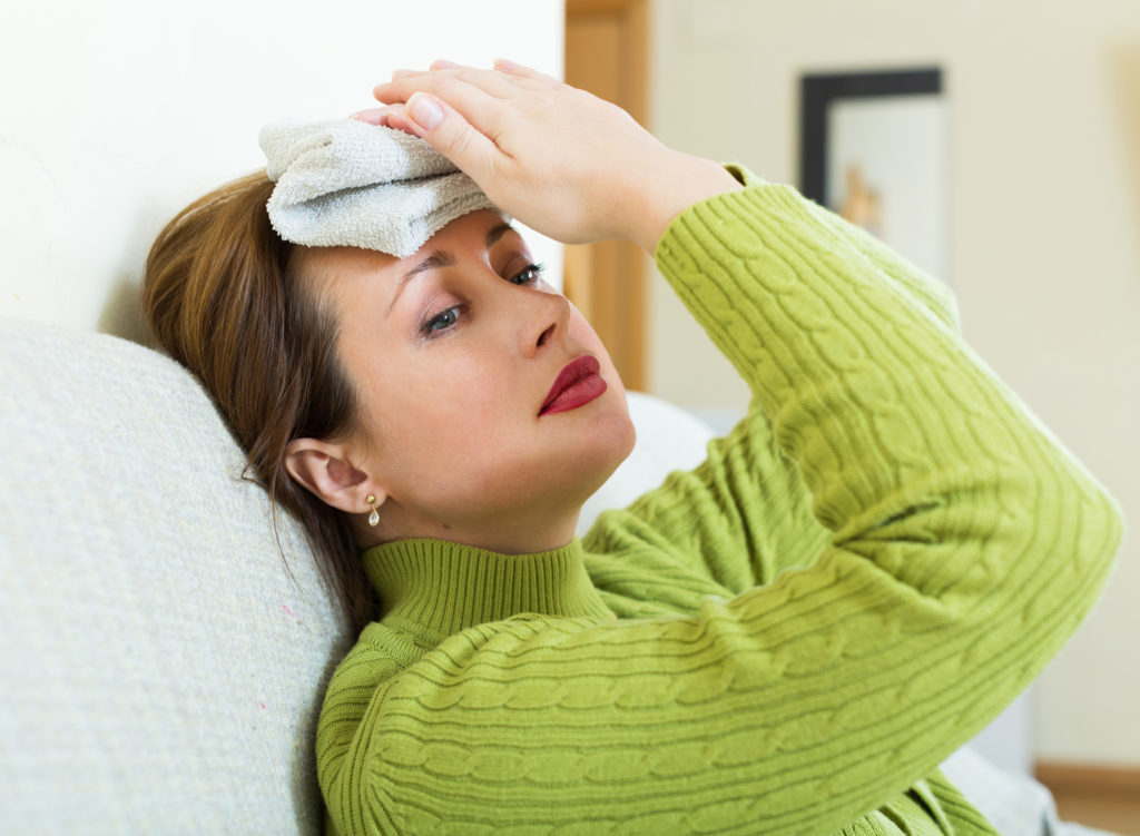 Sick female with huge migraine holding wet towel on her head ;