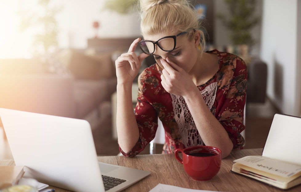 Woman sitting in front of laptop rubs her nose as she looks down
