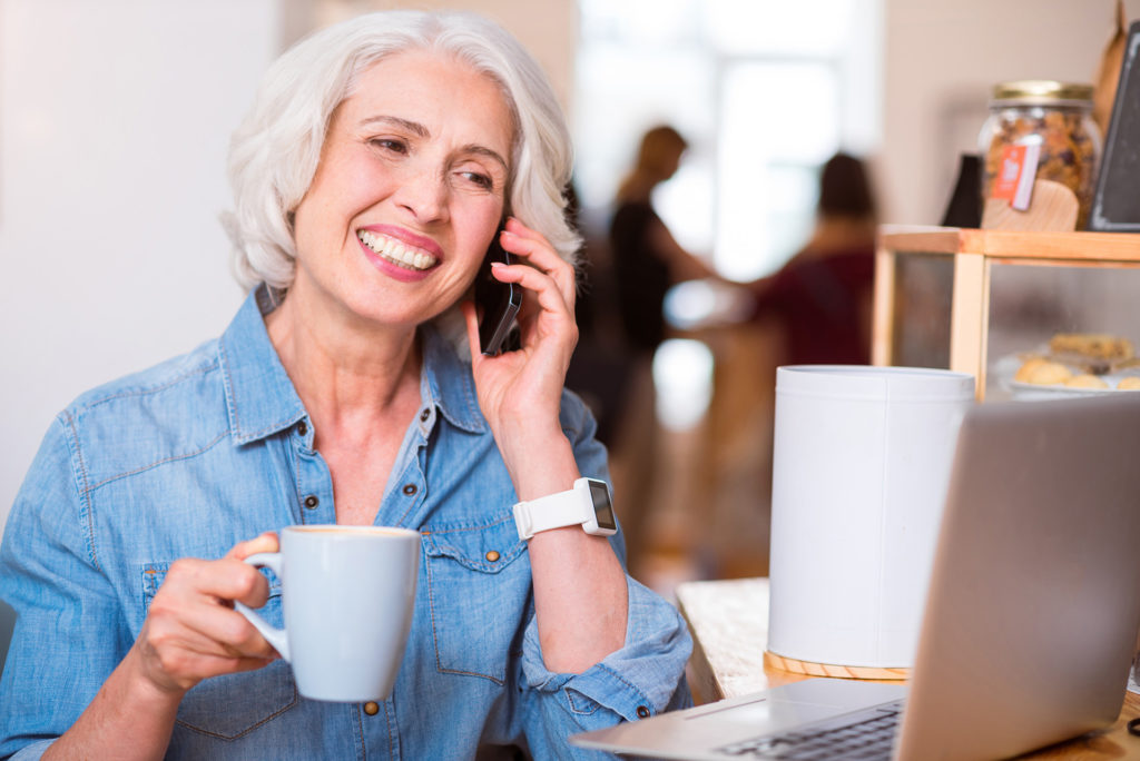 Positive woman talking on cell phone;