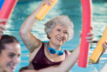 Smiling senior woman doing aqua fitness with swim noodles. Happy mature healthy woman taking fitness classes in aqua aerobics. Healthy old woman holding swim noodles doing aqua gym with young trainer.;