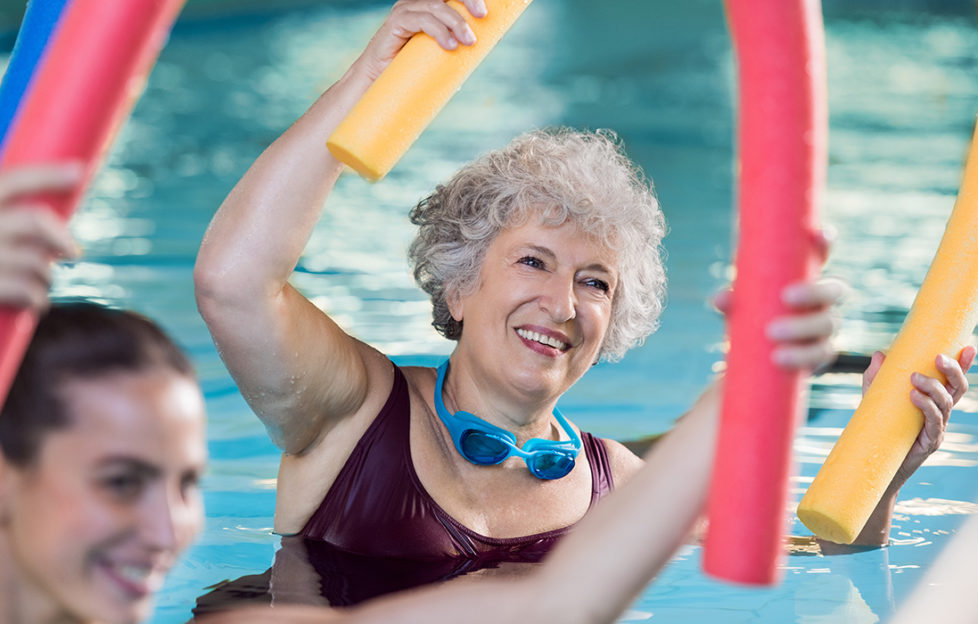 Smiling senior woman doing aqua fitness with swim noodles. Happy mature healthy woman taking fitness classes in aqua aerobics. Healthy old woman holding swim noodles doing aqua gym with young trainer.;