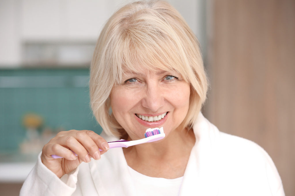 Mature woman cleaning teeth at home;