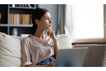 Woman staring past laptop in her living room