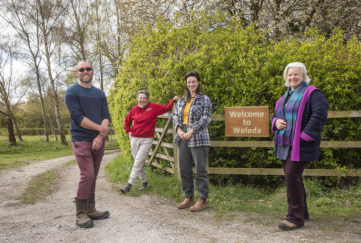 4 people standing by farm gate, wooden Weleda Garden sign