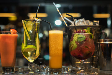 Glasses of different cocktails on bar background; World Cocktail Day
