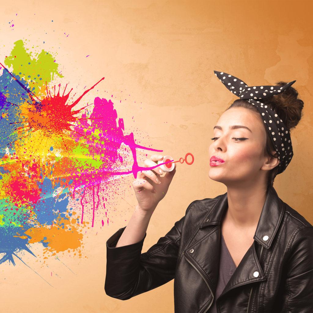 Cute girl blowing bubble spalsh graffiti onto wall; une 5