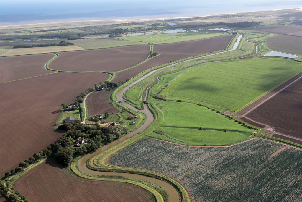 Aerial view of river through flat landscape to the sea, Lincolnshire fens, which inspire crime author Joy Ellis
